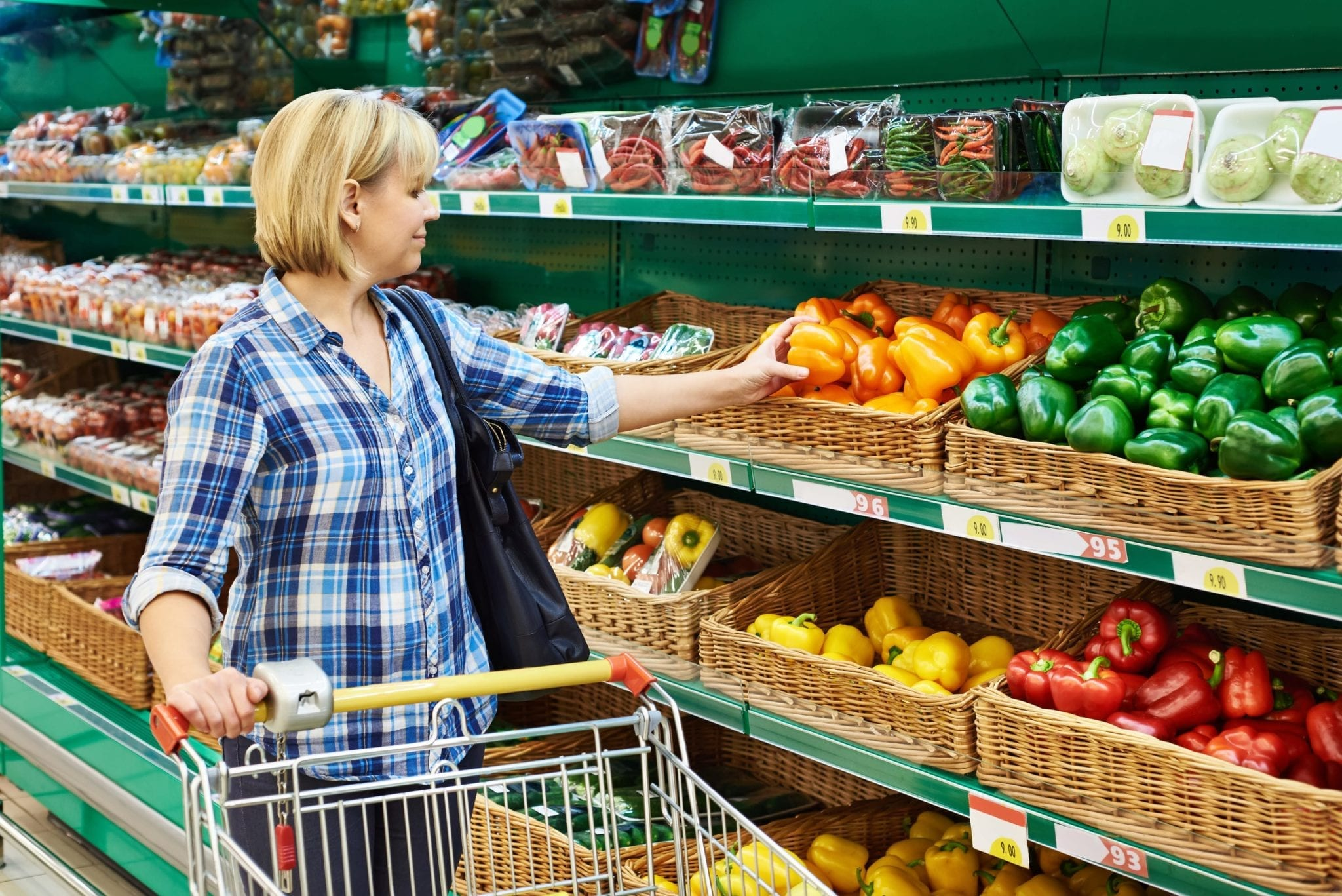 Woman buys bell peppers in store